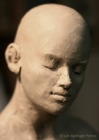 A Good Read©Lori Kiplinger Pandy. Close up photo of clay sculpture work in progress, bald girl's face.