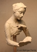 A Good Read ©Lori Kiplinger Pandy. Rough clay sketch of a girl reading a book - maquette.