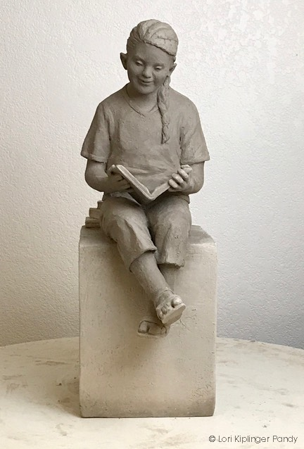 Ceramic sculpture of girl with Down syndrome Reading ©Lori Kiplinger Pandy