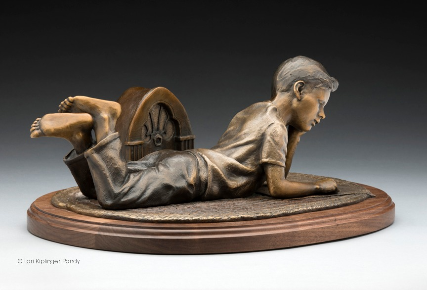 Bronze sculpture of little boy reading Sunday Comics to 1940's radio © Lori Kiplinger Pandy